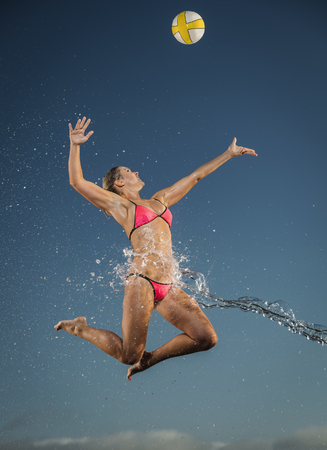 Water splashing on Caucasian woman jumping to volleyball