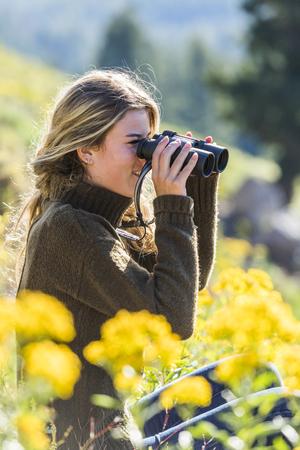 Caucasian girl in field using binoculars Banco de Imagens - 102038036