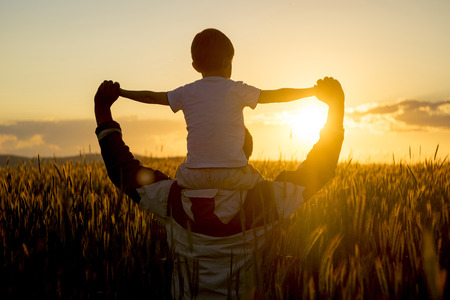 Father carrying son on shoulders in field of wheat at sunset LANG_EVOIMAGES