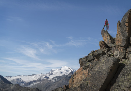 Distant Caucasian man standing on mountain rock