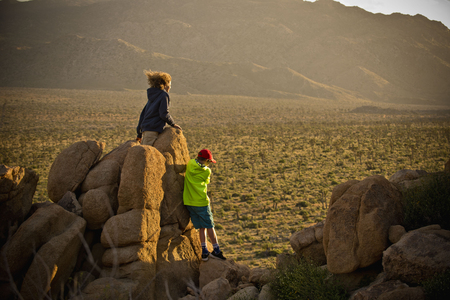 Boys standing on rocks admiring desert landscape