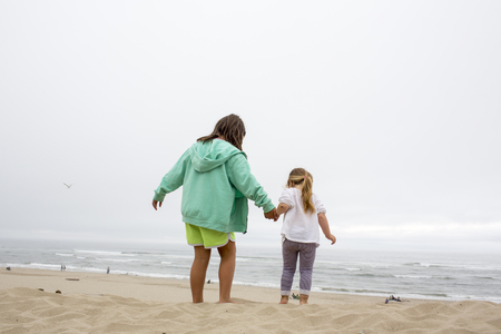 Caucasian mother and daughter holding hands on beach