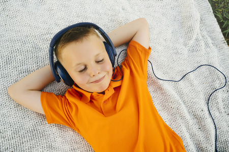 Smiling Caucasian boy laying on blanket in park listening to headphones