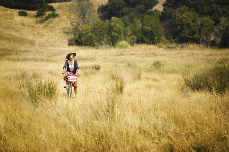 Caucasian woman riding bicycle in field Banco de Imagens - 102038039