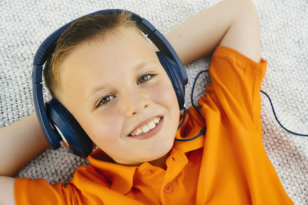 Smiling Caucasian boy laying on blanket in park listening to headphones Banco de Imagens - 102038042