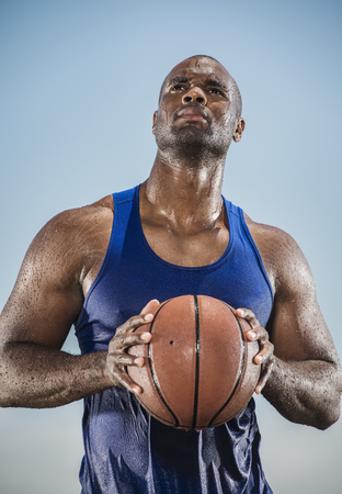 Pensive sweating Black man holding basketball