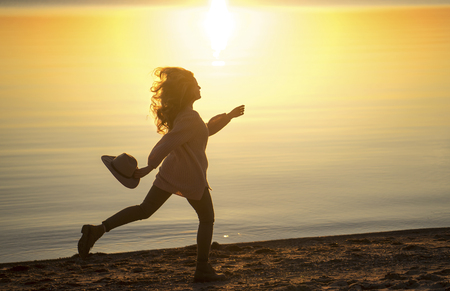 Caucasian woman running on beach holding hat Banco de Imagens - 102038044