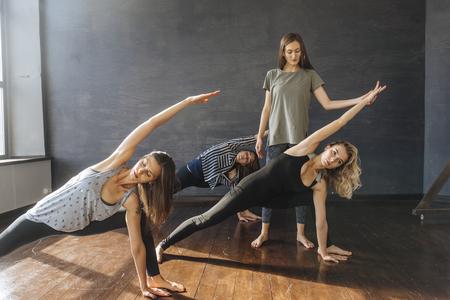 Instructor watching Caucasian women stretching arms in yoga class Banco de Imagens - 102038046
