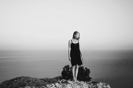 Caucasian woman standing on rock near ocean Banco de Imagens - 102038050