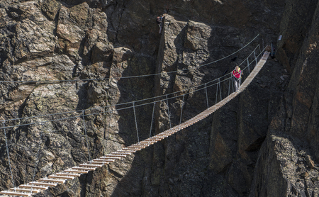 Caucasian man crossing rope bridge on mountain