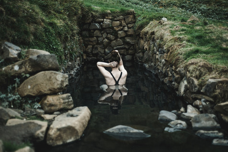 Caucasian woman swimming in pond Banco de Imagens - 102038052
