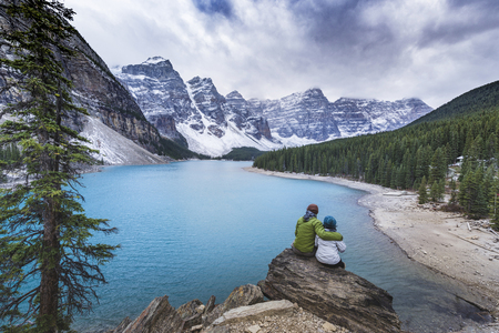 Asian couple sitting on rock admiring scenic view of mountain lake Banco de Imagens - 102038053