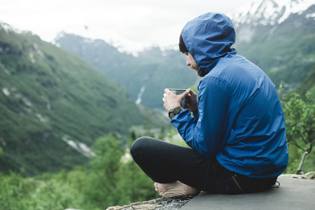 Caucasian man sitting in mountain landscape drinking coffee