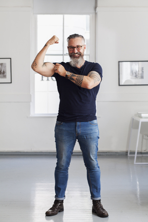 Smiling muscular Caucasian hipster man flexing biceps