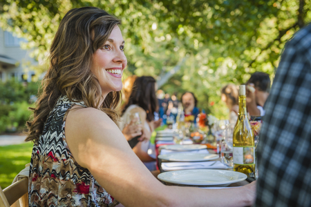 Portrait of smiling Caucasian woman sitting at table at party outdoors