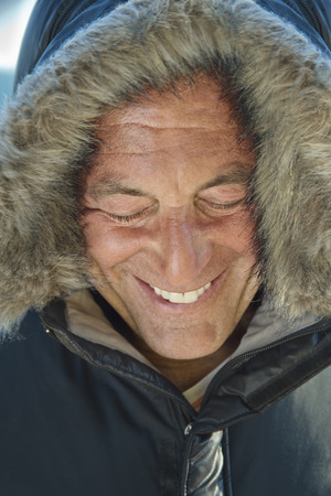 Smiling Caucasian man wearing coat with fur hood