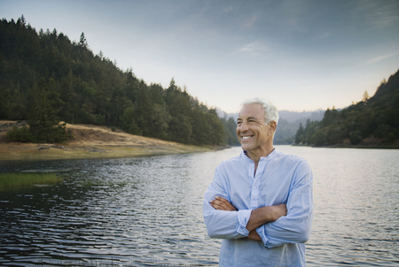 Smiling Caucasian man standing near lake