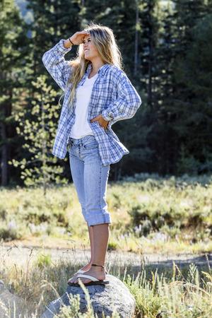 Caucasian girl wearing plaid shirt standing on rock Banco de Imagens - 102038072