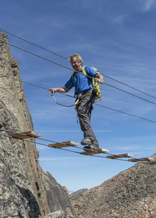 Caucasian man crossing rope bridge on mountain Banco de Imagens - 102038085