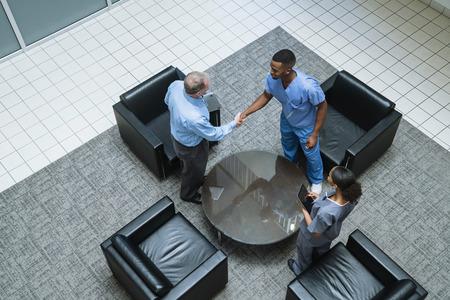 Doctor and nurse shaking hands in lobby Banco de Imagens - 102038088