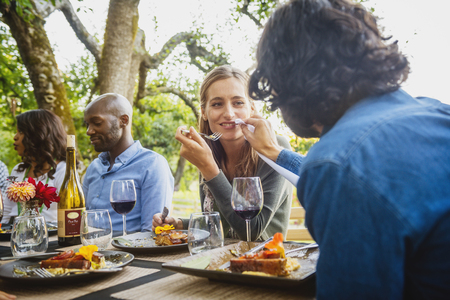 Man feeding food to woman at party outdoors