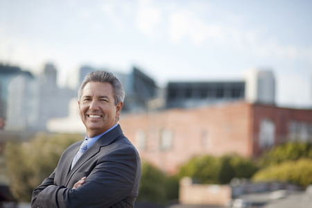 Portrait of smiling Hispanic businessman posing outdoors