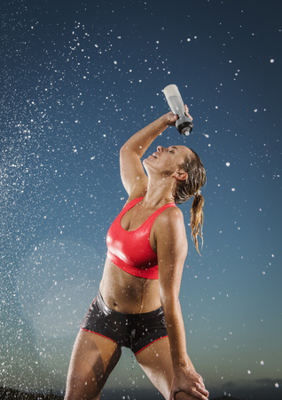 Water splashing on Caucasian woman cooling off with water bottle