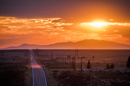 Cars driving on remote road at sunset Banco de Imagens - 102038101