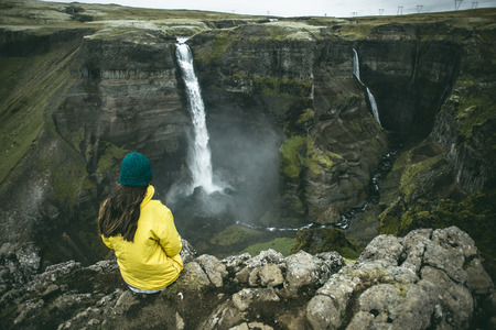 Caucasian woman sitting on cliff admiring waterfalls
