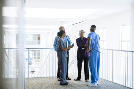 Doctors and nurses talking near staircase LANG_EVOIMAGES