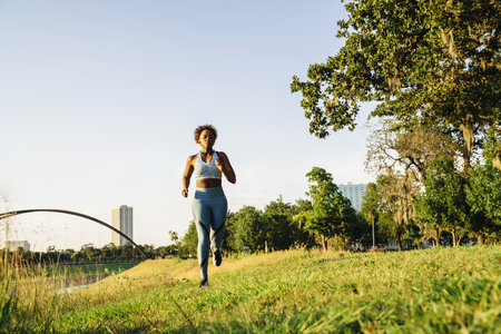 Mixed Race woman running in grass near waterfront
