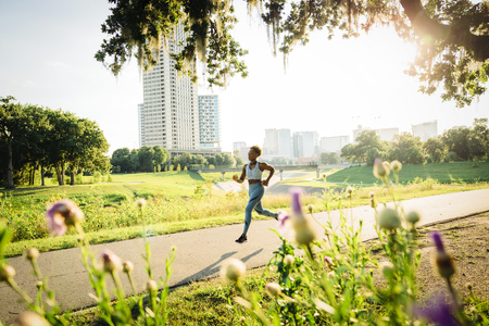 Mixed Race woman running on path in park beyond wildflowers Banco de Imagens - 102038106