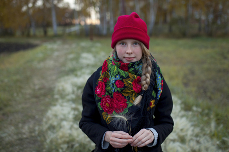 Portrait of Caucasian woman wearing scarf and stocking-cap holding hay seed LANG_EVOIMAGES