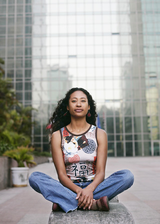 Portrait of serious mixed race woman sitting near highrise
