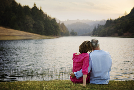 Couple sitting in grass and hugging near river Banco de Imagens - 102038118