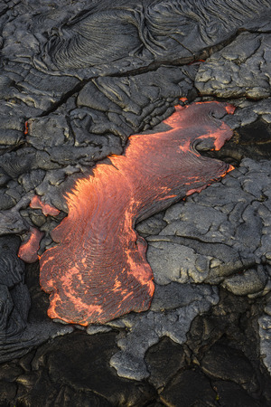 Molten lava glowing near dried lava