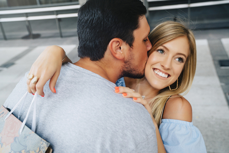 Caucasian man kissing cheek of woman carrying shopping bag LANG_EVOIMAGES