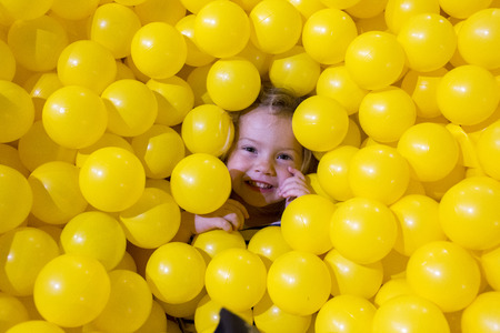 Caucasian girl laying in pile of yellow balls LANG_EVOIMAGES