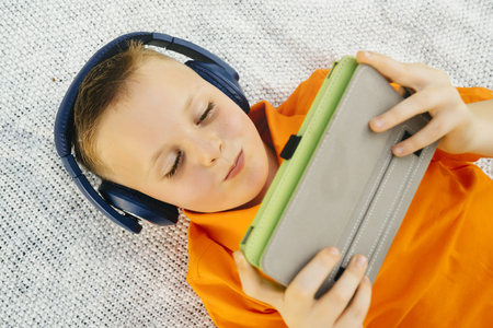 Smiling Caucasian boy laying on blanket listening to digital tablet