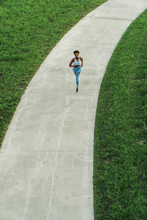 Distant mixed race woman running on path in park