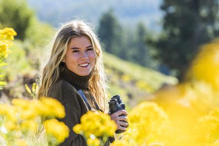 Caucasian girl in field holding binoculars