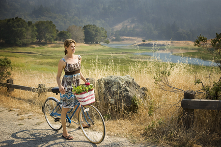 Smiling Hispanic woman standing with bicycle near river
