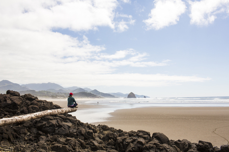 Caucasian woman sitting on log on rocks at beach