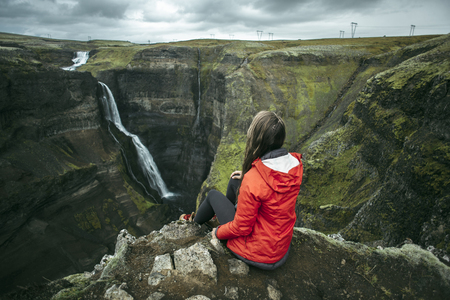 Caucasian woman sitting on cliff admiring waterfall Banco de Imagens - 102038132