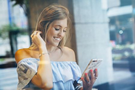 Smiling Caucasian woman texting on cell phone Banco de Imagens - 102038143