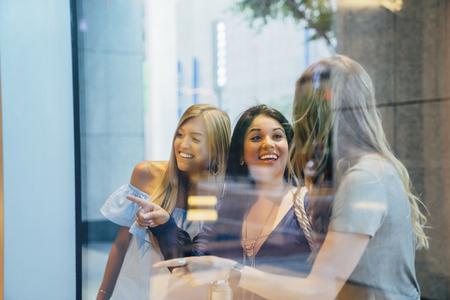 Smiling women window shopping