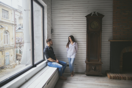 Caucasian couple hanging out near window