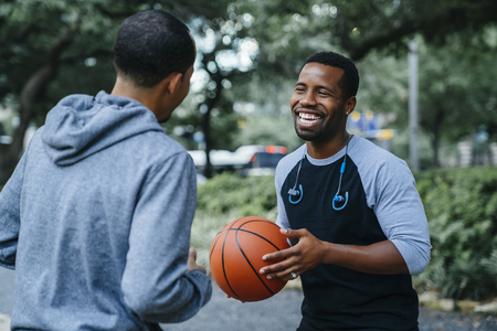 Smiling Black men playing basketball