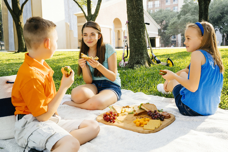 Smiling Caucasian brother and sisters eating food at picnic LANG_EVOIMAGES