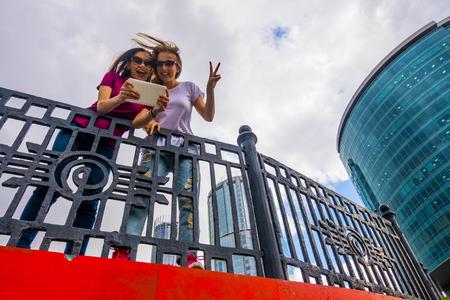 Caucasian women posing for selfie near railing using digital tablet